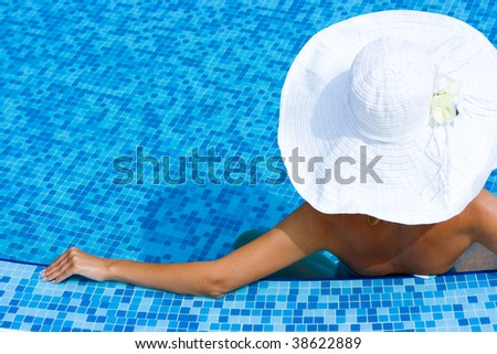 Girl in white hat sitting in the swimming pool - stock photo