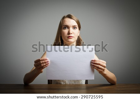 Girl in white holding white paper in her hands. - stock photo
