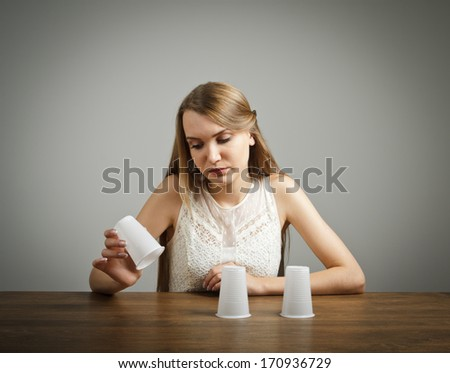 Girl in white is trying to guess what is under the cups. - stock photo