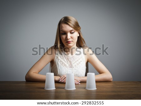Girl in white is trying to guess what is under the cups.