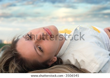 girl in white lays under the sunset cloudy sky