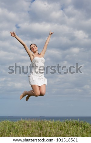 Girl in white on open air. Attractive young woman in white dress jumping on background of sky