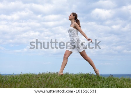 Girl in white on open air. Attractive young woman in white dress running along field