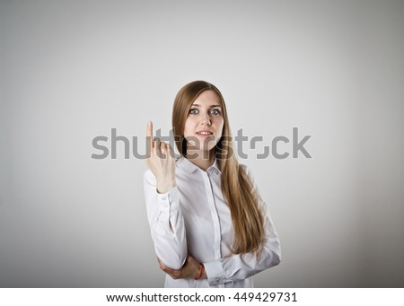 Girl in white pointing at something interesting on grey background. - stock photo