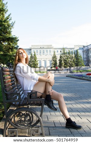 Girl in white shirt and shorts sitting on a bench in the park