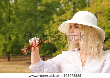 Girl in white shirt and straw hat holding sunglasses in her hand looking into the distance - stock photo