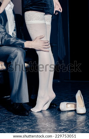 girl in white stockings seduces man indoors. Embrace the men and women in a restaurant. prelude to sex. - stock photo