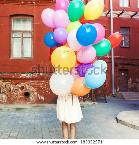 girl in white summer dress hides herself behind a bunch of balloons