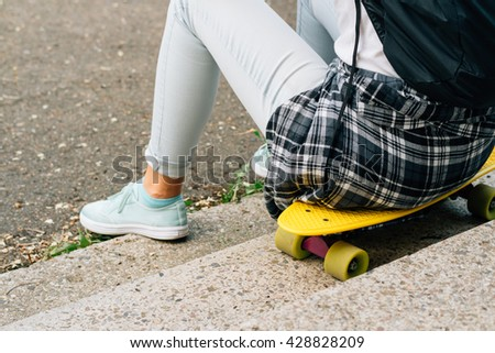 Girl in white T-shirt and jeans sitting on the yellow plastic skateboard - stock photo