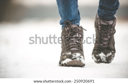girl in winter boots walking on snowy road - stock photo