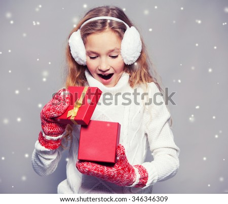 Girl in winter clothes. Happy child with gift. Studio shot