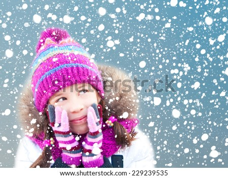 Girl in winter clothes looking at snow - stock photo