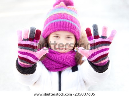 Girl in winter clothes showing her hands with gloves - stock photo
