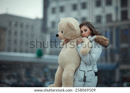 Girl in winter during snowfall is in the city. She cuddle toy bear, her eyes closed and a sad face. Photo with open aperture and soft focus. Photo toned. - stock photo
