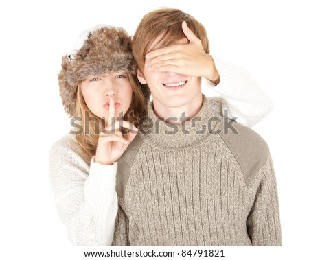 girl in winter hat covering her boyfriend's eyes to surprised him and gesture silent