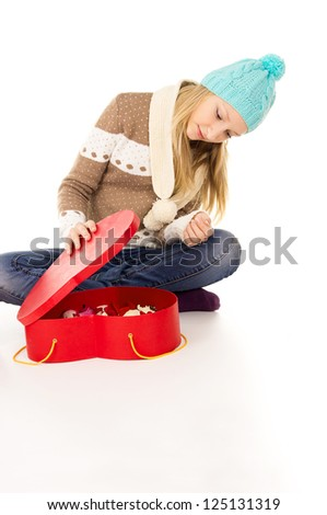 girl in winter hat sitting with gift boxes isolated on white background - stock photo