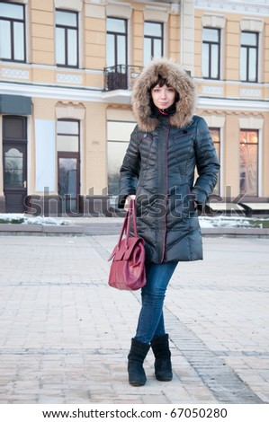 Girl in winter jacket on the street - stock photo