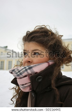 girl in winter near yellow building in St-Petersburg - stock photo