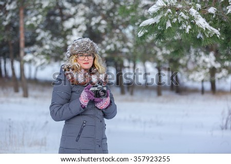 Girl in winter park on a retro camera photographs, photographer winter,