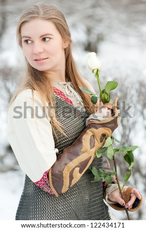Girl in winter park with live rose - stock photo