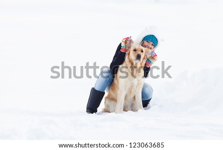 Girl in winter suit on a walk with her labrador. Girl in winter outdoors. Girl with Labrador Retriever.