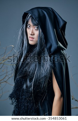 girl in witch costume and black cloak