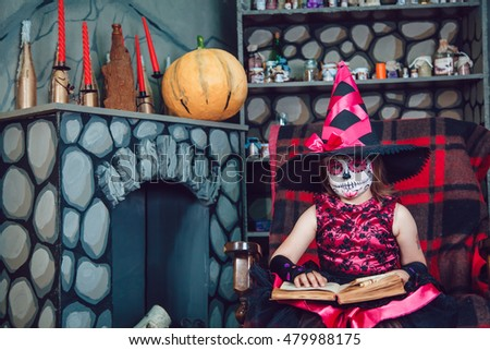 Girl in witch costume and make-up on her face sitting in a chair with a book in his hands in halloween decorations