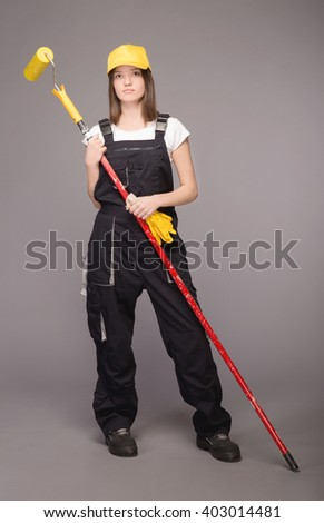 Girl in working clothes in a baseball cap with gloves and a long paint brush in hand. Gray background.