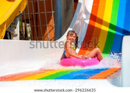 Girl in yellow bikini in beach ring sliding water park. - stock photo