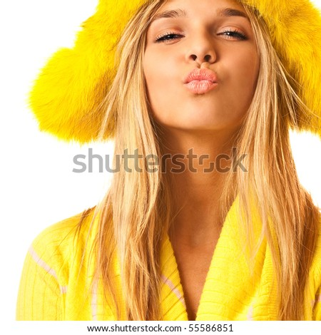 Girl in yellow fur cap sends an air kiss. - stock photo