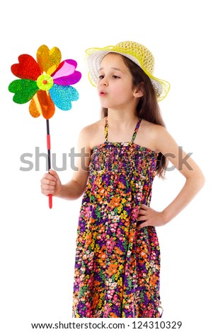 Girl in yellow hat blowing to windmill, isolated on white