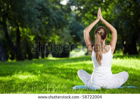 Girl in yoga pose in the park - stock photo