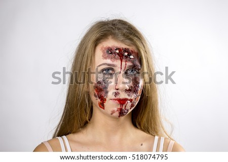 girl in zombie make-up, face close up, bloody wounds on face, on a white background