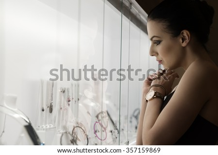 girl inside a shop , in ambient natural light looking some jewelery ,