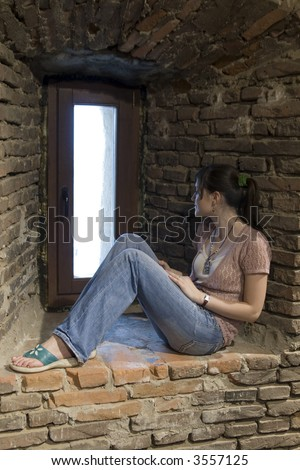 Girl inside a tower watching from the window - stock photo