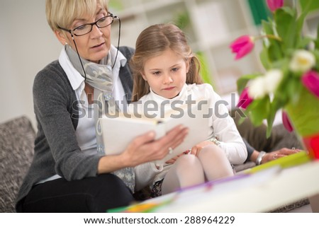 girl interested looks at the book which her grandmother read - stock photo