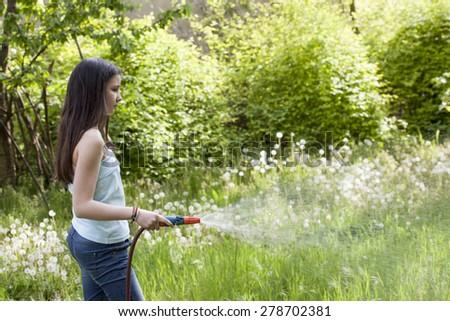 Girl irrigate the grass in the garden  - stock photo