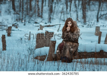 Girl is breathing on his hands warming them in winter. - stock photo