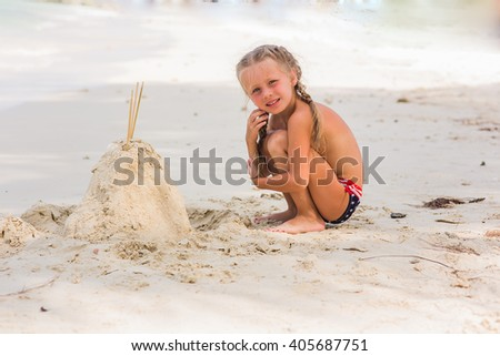 Girl is building on the beach sandcastles in the summer sunny day - stock photo