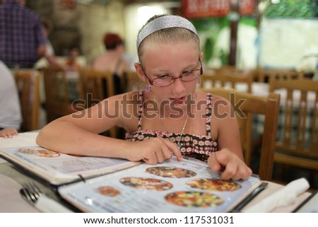 Girl is choosing dish in a restaurant at night - stock photo