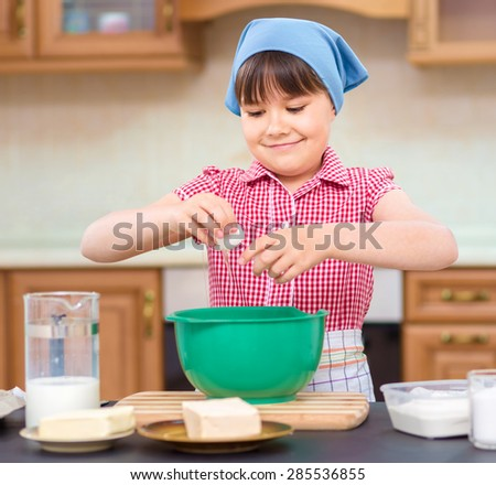 Girl is cooking, breaking eggs, indoor shoot - stock photo