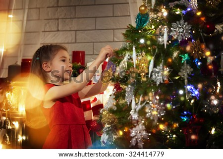 Girl is decorating the Christmas tree - stock photo