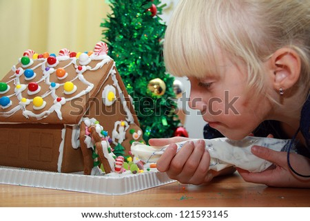 Girl is decorating the gingerbread house - stock photo
