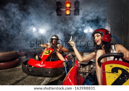 girl is driving Go-kart with speed in Karting. Aggressive woman indicating finger - stock photo