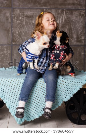 Girl is embraces two small chuhuahua dogs - stock photo