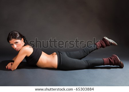 Girl is engaged in fitness lying on a black background