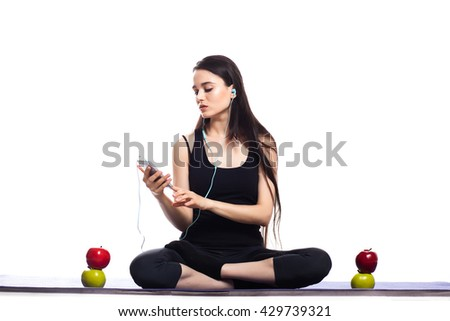 Girl is engaged in yoga on a white background, music, headphones, phone, player - stock photo