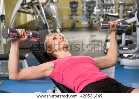 Girl is engaged on simulators in gym - stock photo
