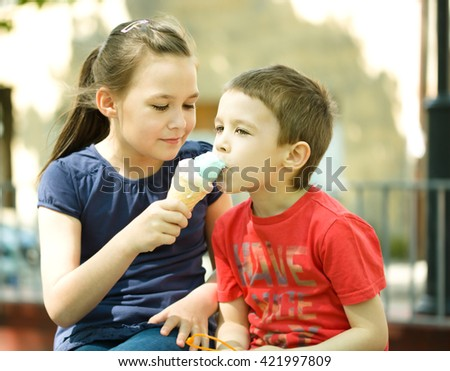 Girl is feeding his little brother with ice-cream. Outdoor - stock photo