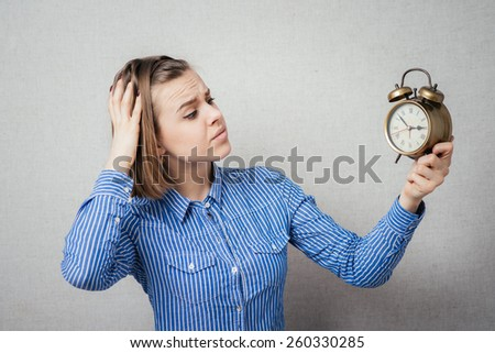 girl is going through and holding a clock alarm clock - stock photo